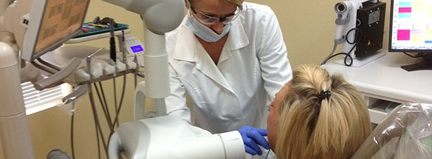 Photo of a dental hygienist with Dr. Tony Hewlett giving a patient a digital radiograph