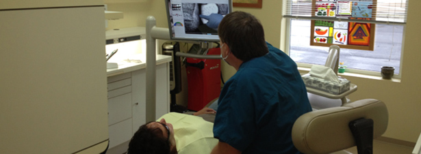 Photo of Dr. Tony Hewlett showing a patient a digital dental radiograph