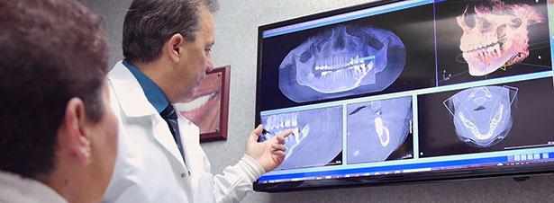 Photo of Dr. Anthony Ramirez showing a patient digital dental radiographs